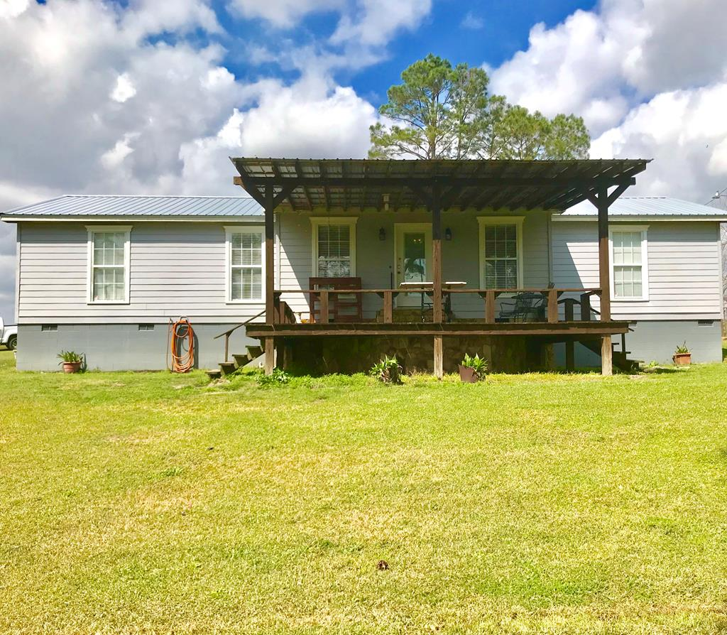 Enjoy the country life in this move-in ready 3 BD/2BA home, nestled on 3.08 acres. As you pull into one of the two gated drives, you are greeted by beautiful pine trees. This property offers a workshop with a lean to on each side, a 1 1/2 horse power well pump & a shooting range for target practice. In addition to planted pines, you'll find pear, peach & pecan trees as well as blueberry bushes & blackberries. Enjoy evenings on the front or back porch watching the sunset. Like to entertain guests? The back porch is a great outdoor entertaining space for friends and family with a firepit close by for the cooler evenings. Home offers kitchen and dining area combo, split floor plan, both baths have tile flooring, carpet in the two spare bedrooms, and St. James Collection laminate wood flooring throughout the rest the home, tankless water heater and corian countertops in the kitchen. Roof, well &  A/C unit replaced in November 2018. Mower is included in the sale. 10 Minutes North of Cairo.