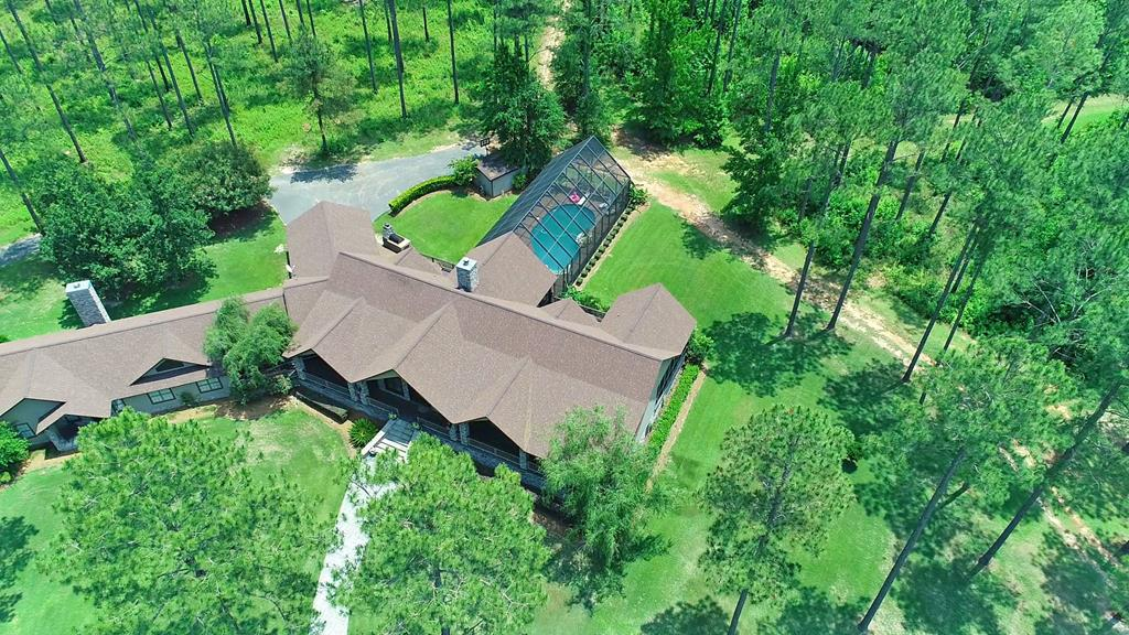 IMPRESSIVE 6,400 sq. ft. home on approx. 40 Acres with a 3 acre stocked lake and 3200 sq ft barn and shop;located in Boston, GA just minutes from Historic Downtown Thomasville in Thomas County. This architecturally designed home has 4 BR/3.5 baths, loads of living space, gorgeous wood throughout, and a grand master suite fit for a king and queen that opens to a screened porch overlooking the lake. Plenty of space for your guests or for an in-law suite. Other deluxe features include a  fitness room, a gun room, and a massive laundry/mud room. You'll love the enclosed Saltwater Pool and all of the outdoor entertaining space.The barn functions as a hobby room and guesthouse and is complete with a kitchen and half bath. The spacious attached shop has a car lift and lots of room for all of your hobbies and equipment storage.Topping off the professionally managed timber and well-kept grounds is the lake with its own well and two fountains that's stocked with trophy fish!