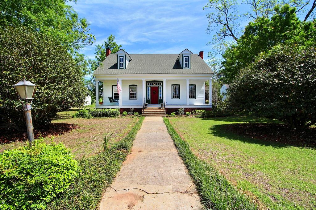 Beautifully restored farmhouse with guest house on 2 acres just outside the city limits! This amazing property has too many features to list. You just have to see it in person and feel the charm for yourself. The home has updated electric and plumbing as well as 2 separate AC units and freshly painted exterior. The original wide plank hardwood floors have been masterfully restored and the home has been enhanced with beautiful crown moldings, tongue and groove ceilings, and updated trimwork. The uniqueness and farmhouse feel of the this home has been maintained with multiple fireplaces, huge screened back porch, and rocking chair front porch. The 960 sqft one bedroom one bath guest house is great for in-laws or extra rental income and has it's own electric and water connections. Don't miss out on this amazing property!