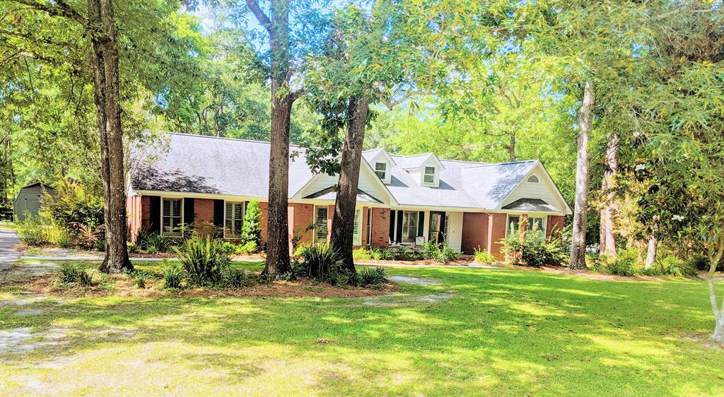 Excellent 3/2 brick home in the wonderful Northwoods subdivision. Owner has taken immaculate care and made many updates since purchase.  This bright open 1 story home has many amenities and large rooms. The master bath is superb and the screen porch and kitchen are great for entertaining.  The den is cozy with a log burning fireplace.  There are 2 closets and an attic in the double expanded garage and an outbuilding in the backyard.     New owner added crown molding, 4 motion detectors, new stove top, new hardware in the kitchen, painted the cabinets, added plantation shutters throughout the house, added additional landscape and a new chimney cap.