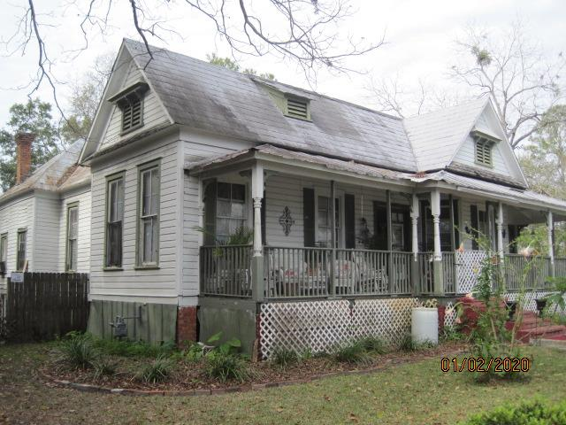 Lovely older home that is just waiting for a little tlc.  Has wood floors throughout, nice big rooms, wonderful porch areas in front and side, big kitchen for cooks and guests.  Pocket doors and high ceilings make this a desirable find.  Mature landscaping with fruit trees and outdoor storage on a corner lot.