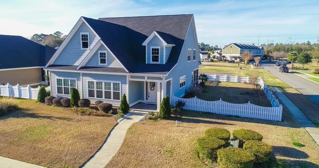 Impressive & on a rare corner lot in popular Madison Grove Subdivision.  This spacious 3,077 sq ft. home features a lrg family room w/ double sided gas fireplace that can also be enjoyed from the dining room. The kitchen is conveniently located just off  the family room & has a center island that can be used for extra seating & preparing meals.  With miles of cabinets, theres a place for all the cooks gadgets. The master suite features a lrg bath that includes a luxury shower, soaking tub, his & her vanities, & walk-in closet.  A convenient 2nd bedroom & bath are located downstairs.  Gorgeous granite counters, hardwood floors, high ceilings, & thick crown molding are located throughout the home. Upstairs has a large bonus room, 2 additional bedrooms and a common full bath. Guests will have plenty of parking space directly behind the home in the only extra parking area in Madison Grove.   Also enjoy the screened porch, fenced side yard, clubhouse, pool, catch & release pond. 1 owner!