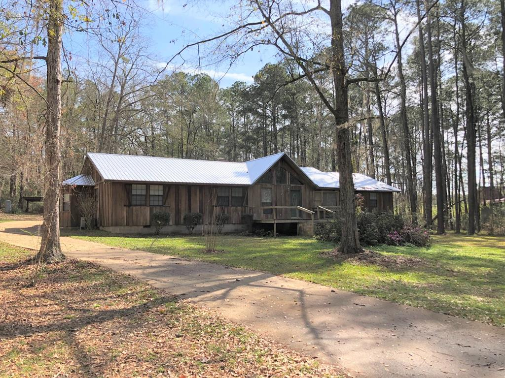 Absolutely beautiful 4 BR, 3 BA log cabin style home on 1.29 acres!!! You don't have to travel to North Georgia to find a gorgeous log cabin style home, this one has heart pine floors throughout as well as soaring vaulted ceilings with tons of recessed lighting! This home also has two large master suites, with spacious bathrooms; great room has a huge ceiling and a massive stone fireplace, that goes all the way up to the ceiling! This home also has tons of space, kitchen also has hardwood floors with a large stainless steel double oven and lots of cabinets. Both master bathrooms have double vanities, one of the master bathrooms has a gorgeous jetted tub with a large and spacious walk-in closet. The acreage is heavily wooded as well as private; property begins with a long, winding road that takes you to the secluded long cabin style home.There is also a huge 20X20 wired workshop; and 2 carports; home has a brand new metal roof and 2 A/C units. Don't miss out on this one! Price Reduced!!