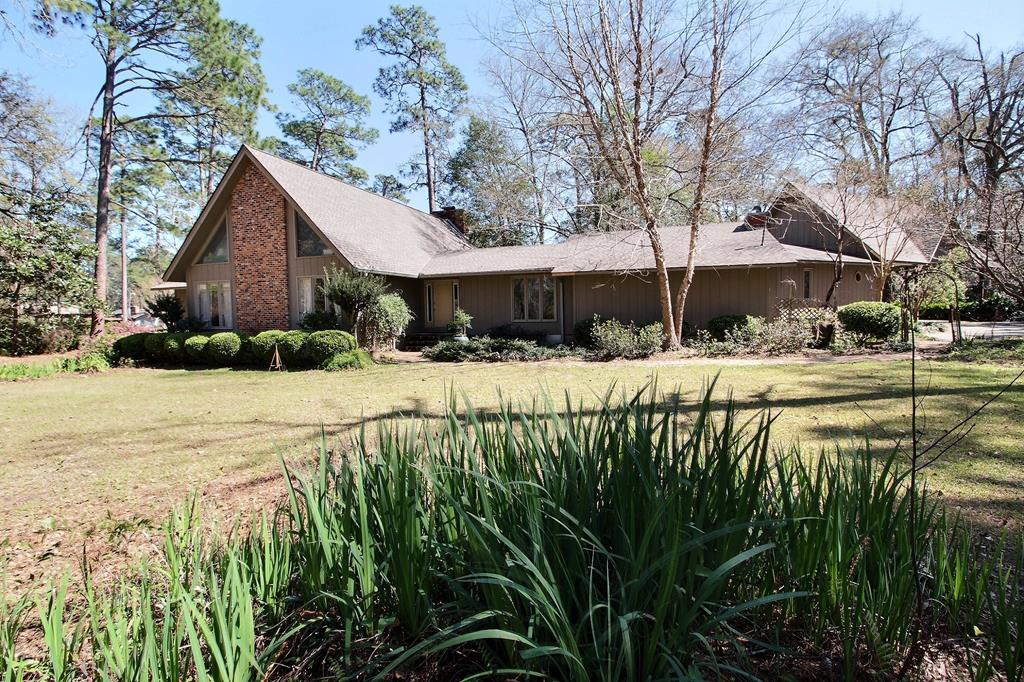 This 4 BR/3.5 BA custom built home has over 3575 square feet and is located on 1.59 acres in Tall Pines subdivision. Large beautiful family room w/ vaulted and beamed ceiling has cypress walls and ceiling, large fireplace, and hardwood floors.  Large open kitchen and breakfast area w/ tile backsplash and center island. Separate dining room w/ walnut wood wainscoating. Split floorplan with two master suites. Main master has hand crafted pecky cypress doors and walls, fireplace, custom built-in desk and bookcase, double vanities, and new custom tile shower. There is also a large loft off family room that would make a great office or upstairs play room. Large back deck off the dining room w/ a covered outdoor cooking area and a custom BBQ. 3 car carport w/ upstairs storage above the carport. Workshop w/ concrete floor, boat storage, electric and water.  House has brand new roof, fruit trees, and mature landscaping. Quiet, fairly secluded area, w/ lots of potential.Call for an appointment.