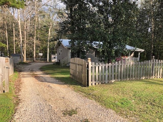 This rustic home has three bedrooms, two and a half baths and a bonus room that would be great as a home office or playroom. All of this is located on approx. 0.74 Acres and is fenced in. The majority of the interior walls and ceilings are tongued and groove pine. The living room features a beamed ceiling, tile flooring and build in bookshelves. The dining area and kitchen are open to the living room. A screened in porch with additional storage is on the back of the house overlooking the spacious yard. There is a fenced in dog kennel area, along with a storage shed. This home is priced to sell. Please call for a private showing.