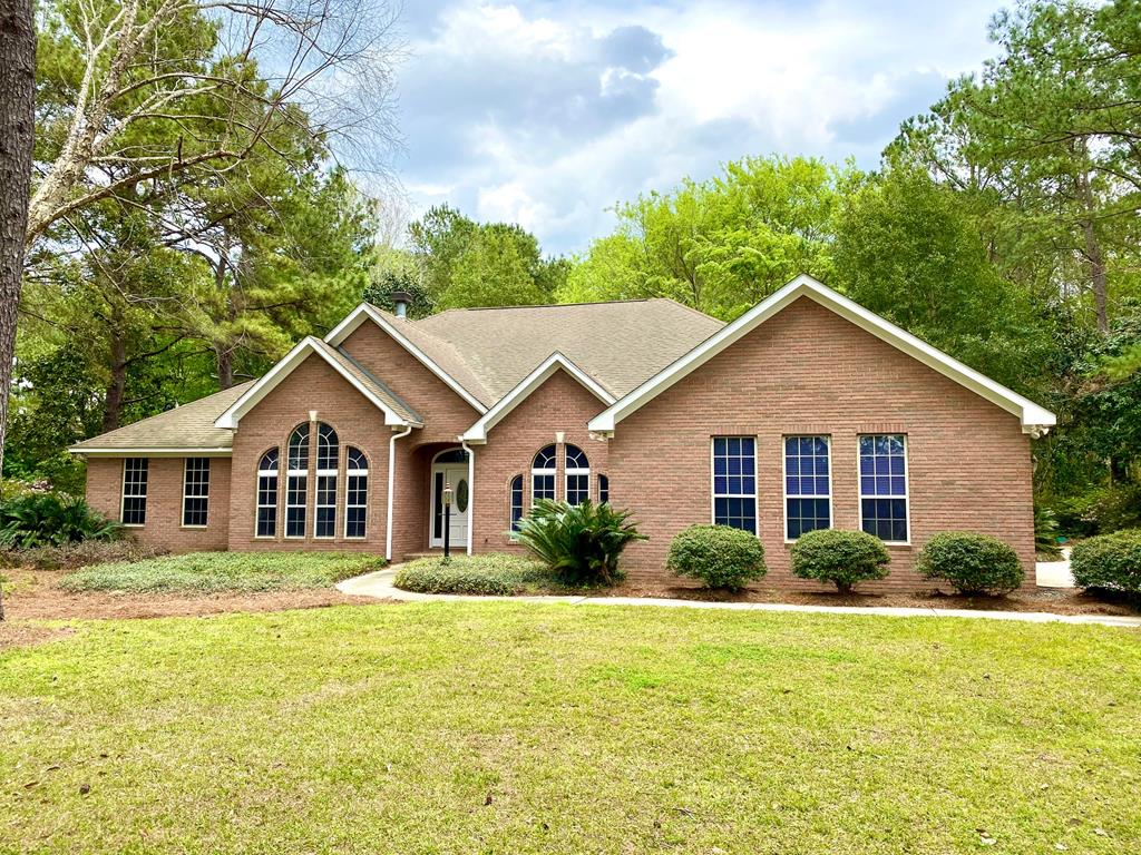 This beautiful brick home in A Place In The Woods sits on 1.3 acres and has everything you've been looking for. The split floor plan offers 4 bedrooms and 3 bathrooms with 2 master suites. It has a formal dining room and sitting room, a large family room with wood burning fireplace with built-in cabinets and bookshelves on each side of the fireplace. The spacious kitchen has new appliances and tons of cabinet space for storage. The main master bedroom features his and her closets, separate vanities, a tiled walk-in shower, large jetted tub and french doors leading to the back covered porch and patio area. The home has lots of closets for storage as well as an oversized garage. The backyard is absolutely huge with a fabulous tiled patio that's perfect for a fire pit and good friends.
