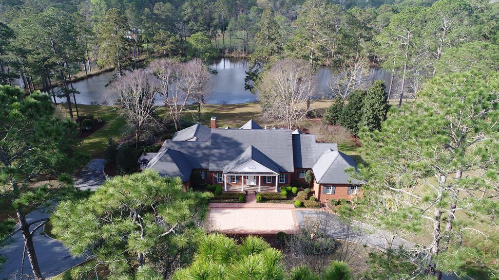 This custom home has been meticulously maintained and thoughtfully designed to accommodate family and guest. Located on Spring Lake, the home boasts over 6000 square feet of living space and includes 5 bedrooms, 4 baths, and 2 half baths. Keen attention to detail can be found throughout the house. A mahogany paneled study, complete with fireplace,  is located off of the front foyer. The living room is showcased by the custom Palladian windows that take in the views of the terrace and lake beyond. The spacious gourmet kitchen features granite counters, stainless steel appliance and custom cabinets. A sunroom, with vaulted ceilings of pickled pine and built-in bookcases, creates a welcomed environment to relax and view the tranquil lakefront setting. The downstairs master suite features separate his and her bathrooms, a private office, and exercise room complete with sauna. Additionally, a guest suite is located on the ground level.