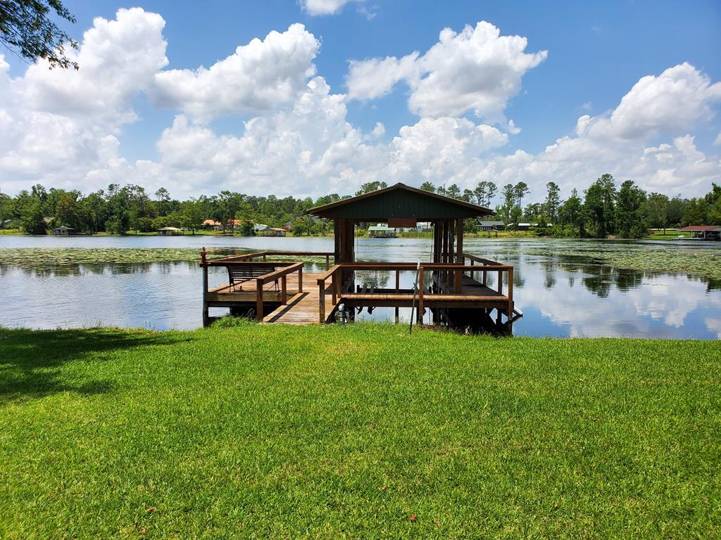 Well kept home on beautiful Lake Seminole! While entering this home you will find a great room with wood floors, gas fireplace and windows across the back of the house to see a view of the lake. The Kitchen offers stainless steel appliances and plenty of cabinet space. The Laundry room is right off of the kitchen near the master suite with a half bath coming in from the 2 car garage. Master suite consist of a walk in closet and double sinks in the master bath. This split plan home also offers 2 additional bedrooms with a full bath. Magnificent screened in porch to sit and enjoy early morning coffee and late afternoon sunsets. 2 car garage with concrete circle driveway.. Unattached is a workshop/garage as well as a storage building. Powered and ready to be used for all of your play toys. Landscaping surrounds this property, with sprinkler system. Lets not forget to mention the amazing covered dock with boat lift.
