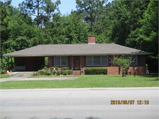 This is such a cute house with so many possibilities  LOCATION and ALL BRICK  3 bedrooms, 2 full bath home has beautiful SOLID WOOD PANELING, solid wood kitchen cabinets, includes refrigerator, microwave, cooktop, wall oven, washer, dryer, hardwood floors, a real fireplace and a ONE YEAR HOME WARRANTY!  The roof was replaced within past year with architectural shingles.  Nice sized front yard, beautiful roses, 2 vehicle carport, storage area with laundry,LARGE BACKYARD and a SEPARATE STORAGE BUILDING all on .53 acres close to everything.  Whether you want to personalize and make it all yours, or just make a good investment, you need to see this one before its gone.  Call your favorite Realtor and schedule an appointment!