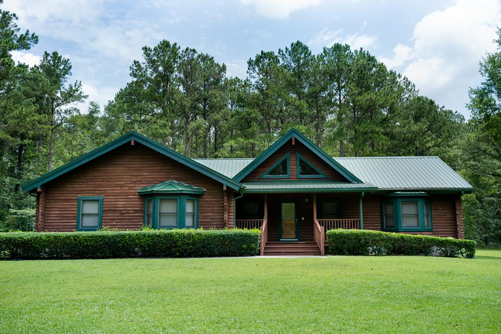 This property is one of a kind for the person that wants to be close to Thomasville yet in the country!  The concrete driveway leads you onto this 8.3 deeded acres that is partially cleared for the home and wooded seclude you from the rest of the world!  The beautiful custom log home has a metal roof with a 3 car garage, front porch with natural landscaping.  Wildlife is abundant and a very good chance to see a turkey or a deer during your morning coffee!  Enter the foyer and you enter the combined living & kitchen area offer a cozy setting with numerous windows with a view, a kitchen layout for the creative cook. The warmth of the wood has a unique eye-catching beauty that you won't want to miss. Hardwood floors takes you two different directions, one to the master bedroom with on-suite bath & very spacious walk in closet and the other to the other two bedrooms & bath.  The quiet & solitude living with close to town conveniences - this home offers it all and more. Don't miss this one!
