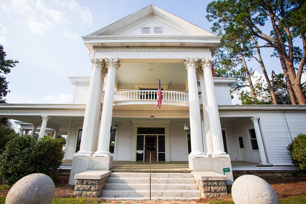 The Pidcock House is an 1890s southern masterpiece of classic architecture. Originally built for the family that brought the railroad to Moultrie, it holds a special position in the towns history and is one the last remaining structures of its stature.  The property consists of the classic manse with intact decorative details and features, a stately carriage house constructed of heart of pine, a freestanding two car garage, and a spacious garden surrounded by concrete pillars and wrought iron railings. This gracious property is walking distance to the courthouse square and redeveloped downtown area.   Property features include: large front porch, double lot, beautiful fencing, and much more.  Call today for easy showing!   Seller is a licensed agent in the state of FL.
