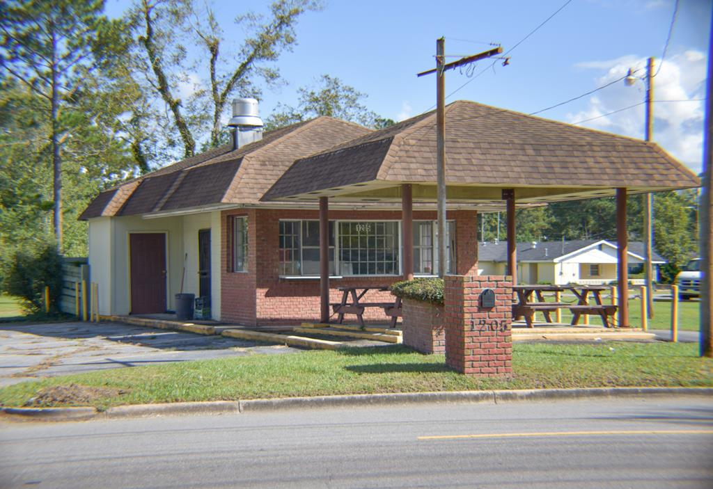 A great property that is perfect for a hotdog/hamburger venue or even an ice cream shop!  Property includes all fixtures and equipment. Upright commercial refrigerator and upright freezer. Triple dishwashing sink, commercial grade vent hood.  Storage area, public restroom on the exterior and private restroom for employees inside. There are two walk-up windows and a covered seating area for customers with power and four picnic benches with tables. Property being Sold AS IS.