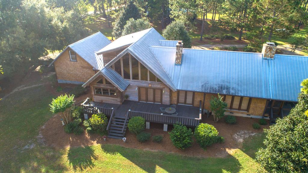 A short drive east of Thomasville sits this unique property with two homes, pond, & several outbuildings on 40 beautiful acres. The main home, a 3223 sf cypress A-frame with metal roof, has beautiful views of the spring fed private fishing pond. Inside you'll find two living areas with wood burning stone fireplaces & cypress walls that create a warm, rustic feel. The large open kitchen, renovated, offers great storage & workspace, 6 burner gas range, double ovens & and pretty views. With 4 bedrooms, 3 1/2 baths & multiple living spaces, there is room for everyone. The screened porch with a third fireplace can be enjoyed year round. Outside is an enclosed outdoor kitchen area lovingly built with reclaimed wood that offers a great entertaining space. Also on the property is a workshop with boat/RV covered storage, a second barn with 3 tractor bays, dog kennel & chicken coop. The 1512 sf second ranch style home across the pond offers 3 bedrooms, 2 baths, and open living/dining/kitchen.