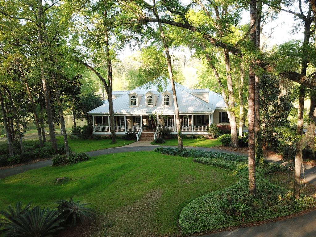 Beautiful and private, this 10 ac. estate offers generous living space and sweeping lake views. The spacious low country style with wide, rocking chair front porch offers a gracious welcome. Notice the reclaimed wood floors salvaged from a local school. Traditional dining & living areas grace the front of the home with comfortable family living spaces along the back. The well-appointed chef's kitchen has a Wolf induction cooktop, twin Thermador ovens, paneled sub zero, ice maker, & more. Retreat to the main level master suite and admire the beauty of the outdoors from the soaking tub or private reading porch. Three oversized bedrooms & 2 baths are located upstairs while the lower level provides ideal bonus space with 2BR/2BA, great room, and full kitchen. Multiple living and entertaining spaces on the main and lower levels flow outside to pristine, natural surroundings. Enjoy basketball or pickleball on your own court!  Matterport 3D Tour: https://my.matterport.com/show/?m=tVB8vDu62sc