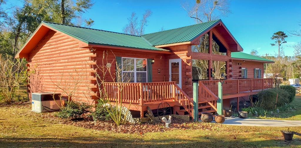 Amazing Cedar Pine Log Cabin Home! Gorgeous 3-bedroom 2 bath, Log Cabin Home offers Privacy & Seclusion. Within walking Distance to Seminole Lake with fishing, boat slips, water sports, an RV Park, and recreational park offering walking trails, tennis courts, & picnic gazebos! You'll love the open layout offering picturesque views overlooking a large rocking chair deck & wooded views. Custom designed kitchen with computer nook, pantry & stainless appliances. Main suite has offers, walk in closet, double vanity sink & jacuzzi tub. Spacious guest bedrooms and bath with jetted tub/shower combo. Over-sized enclosed  sunroom is perfect for lounging or entertaining! New roof and cedar hardwood floors in 2020, metal workshop/storage building with power & covered RV or Boat parking pad. Property includes an adjacent vacant parcel and won't stay on the Market Long! This is a one of a kind home in the area! Grab your Realtor and come see all this home has to offer!