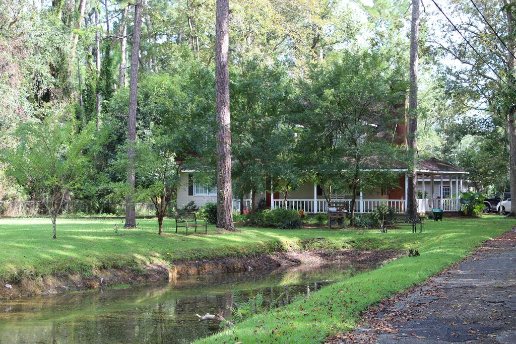 """EXCELLENT LOCATION !!!!  2618 Sq ft Main House with 3 Beds 2 1/2 Baths & Pond Frontage. The property includes an inground sports pool w/ Pool house approx 400 sq ft additional.  This gorgeous property is located on a total of (approx 1.50 acres).  The main house includes approx 1.2 acres with an adjoining lot on the backside of the property that is .31 acres.  The downstairs has a spacious kitchen with an adjoining area that feeds into the dining area.  This spacious floor plan includes a large den with a wood-burning fireplace and built-ins.  The main master bdrm is downstairs and there are 2 bdrms upstairs.  There are 2 road entrances to this wonderful property.  The location is within walking distance to TIRED CREEK GOLF COURSE and is approx 11 mins to TIRED CREEK LAKE which features some of the best fishing around.  The location is convenient to Tallahassee FL (35 Miles)  & Thomasville GA.   This beautiful home does need a little TLC although price appropriately.  Selling """"AS IS."""