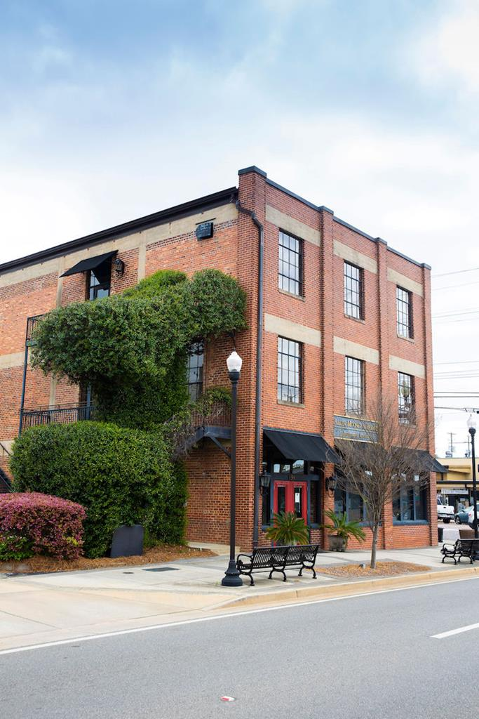 Enjoy all that historic, downtown Thomasville has to offer from this premier 2 bedroom/2.5 bath penthouse. Constructed in 1915, this iconic building was originally utilized as a parking garage to house vehicles belonging to the winter residents. The penthouse occupies the entire top level and consists of approximately 3360 square feet of contemporary living space with exposed bricks, concrete floors, and trusses.  The open floor plan includes a central living and dining room alongside the gourmet kitchen, complete with custom cabinets, sub-zero appliances, warming drawers, wine cooler, and granite counters. A private study/den creates an exceptional work from home (WFH) environment. The gracious master suite has an impressive bathroom with walk-in shower and double vanities as well as his and her closets. The spiral staircase leads to a sunroom and rooftop terrace and provides a one-of-a-kind venue for outdoor entertaining overlooking downtown.