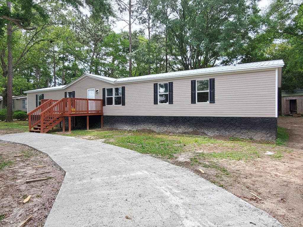 4 bedroom 3 bath doublewide manufactured home over 2400sqft just 2 minutes from the city.  Open floor plan to the formal living room, eat in kitchen and family room with fireplace. The kitchen has island with bar top and walk-in pantry. Primary bedroom separate from the other 3 bedrooms.  The 3 bedrooms share 2 baths on the other end of the house along with an additional living room. Two large decks and brand new metal roof and HVAC.