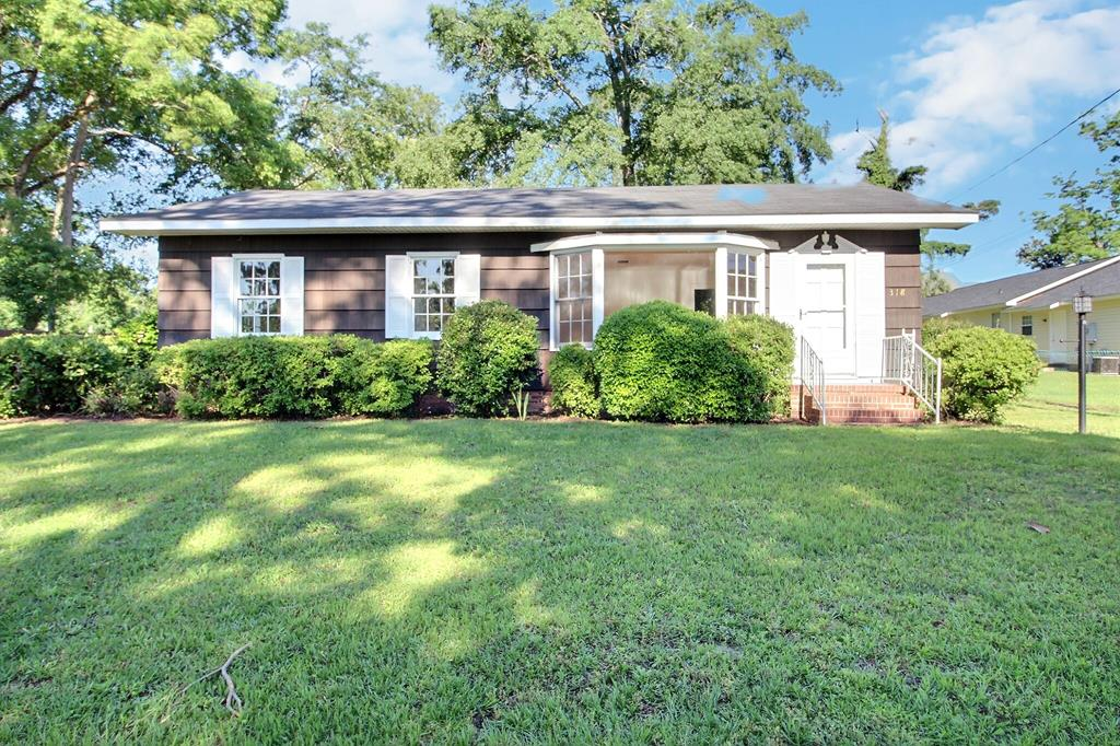 Lovely remodeled cedar-siding cottage on quiet street near schools and downtown featuring a main house with 3 bedrooms/1.5 baths PLUS a separate bonus room with kitchen and full bathroom. Great floor plan that has a formal living room with large bay window plus spacious den off of the kitchen & dining. Upgrades include refinished hardwood floors, fresh paint, new light fixtures (ceiling fans), classic pine paneling in the den and granite countertops in kitchen with abundant cabinet storage & tiled half bath. Plenty of room for entertaining off of the patio or deck to look upon the beautiful camellias and azaleas.  This small lot (.23 acre) allows for easy yard maintenance (partially fenced) but also has large oversized detached 3 car garage with built-in storage shed. Move in ready so call today for an appointment.