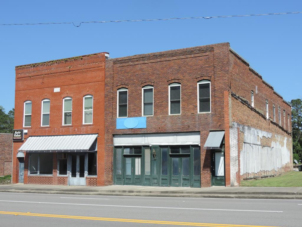 Don't miss out on a unique opportunity to own this versatile building with both residential and commercial options.  Building includes two upstairs apartments and a commercial space on the first floor.  The back apartment features 2 full baths and 2 bedrooms while front apartment is a 2 bedroom, 1 bath unit. Leases are month to month. First floor has over 2,000 square feet ready to be designed to suit and includes two baths. Building has 3 A/C units and 3 meter boxes.
