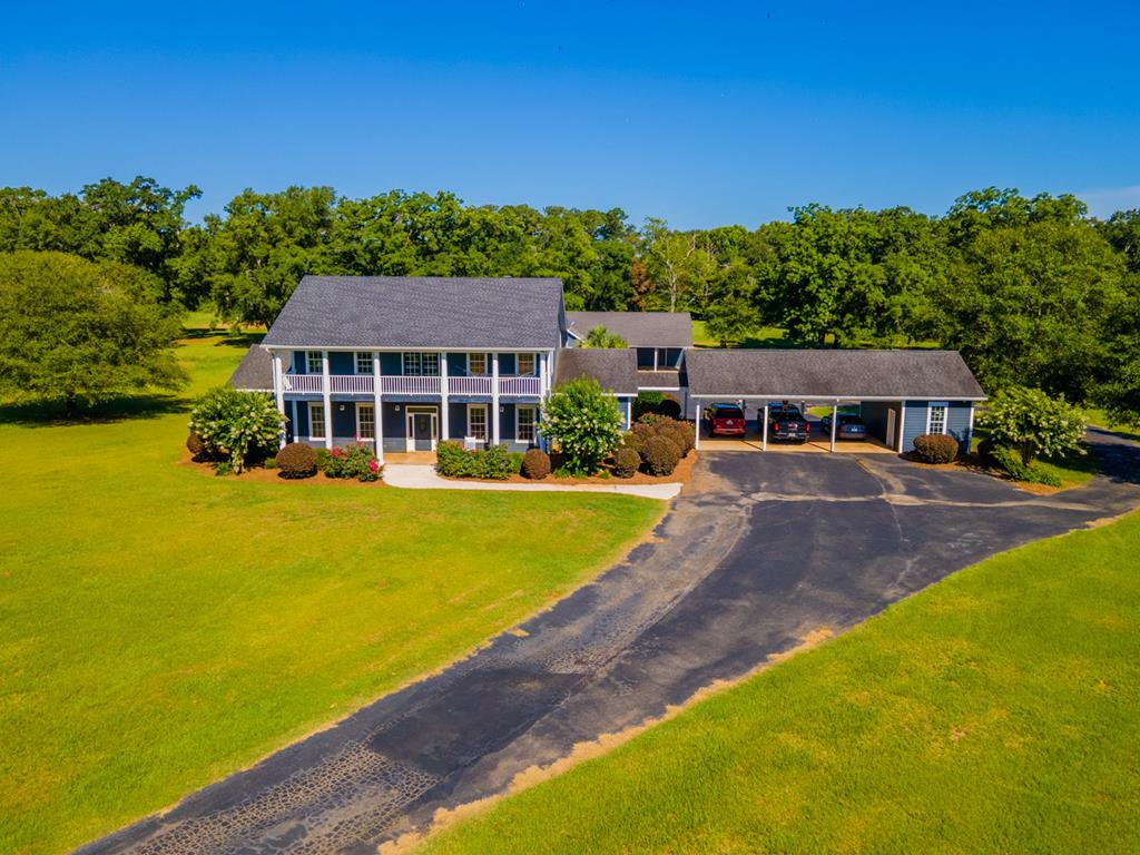 Indulge in a picture-perfect retreat located in Boston, GA with this stunning 24.5-acre property with guest cottage offering a serene hideaway from the hustle and bustle of everyday life. Fully fenced and with room for horses or dog training; you can mix business with pleasure when you call this property your own. The main home  offers a luxurious 4,160 sqft of living space with three bedrooms and 3.5 bathrooms, stone fireplace, pine ceilings and walls, and oversized rooms, plus multiple living areas inside and out including an entertainers oasis. The 1,590 sqft custom guest cottage sleeps up to 10 and is just as beautiful with one bedroom, two full baths, full kitchen, double garage, and all amenities. All appliances are included. The yard is irrigated and the water is provided by a 5 hp deep well.   Your new estate is complete with a 2-acre pond with dock and a saltwater pool; ready for summertime fun. There is a 3,000 sqft enclosed metal barn with electricity, alarm system, camera system, and a central vacuum are also on offer.