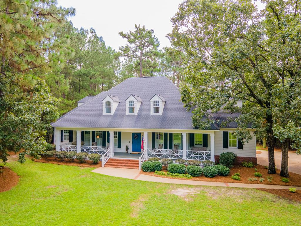 A Southern Living Design by Stephen Fuller, this Low Country Cottage is custom built to ensure a life of elegance and style. Mature trees and a rocking chair front porch welcome you before you step inside to discover a bright and modern 3,612 sq ft layout with soaring ceilings, hardwood floors and high-end finishes. There are four bedrooms and 3.5 baths, plus plenty of living space.  The Owner's Suite is downstairs and offers a very spacious and luxurious bathroom with quartz countertops, walk-in tiled shower, garden tub, and sizeable walk-in closets.  Upstairs, there's 3 bedrooms, two full baths with gorgeous granite countertops and a large bonus room.  A wood-burning fireplace surrounded by built-ins warms the living room while French doors open out to the rear porch. There is a wonderful kitchen with granite counters and loads of cabinet space, plus a dining nook with a gorgeous view over the private backyard. You'll enjoy relaxed evenings on the covered back porch or enjoying smores around the firepit. The garage has been partially enclosed offering an inspired office space. Your new home is set on a 0.79-acre lot with a  fenced backyard, and the adjoining 0.9-acre lot is also available for sale separately for even more space for expansion.  This upscale home is located on the south side of Thomasville in Pebble Creek subdivision, making it convenient to Downtown Thomasville and perfect for Tallahassee commuters.