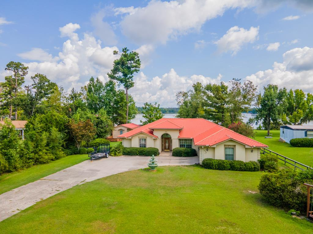 This is one of the most spectacular homes on Lake Seminole!!! This home has been featured on HGTV's Lake Front Bargain Hunt. This 4 bedroom, 2 bath home overlooks Cypress Pond with magnificent views from the all glass windows in the back of the home. This home is very spacious, open and airy with plenty of room for entertaining guests. There is a dining room, living room, great room and a fireplace to keep you warm in the winter. The kitchen features new appliances and a eat at kitchen bar. Master bedroom is large with double vanities, garden tub and separate toilet and shower room. There are three other bedrooms or use one as an office. Outside you will find a separate building finished for your man/woman cave, fenced yard, boat dock and enclosed boat house. Great views of the sunset!!! Call today for your showing!!!
