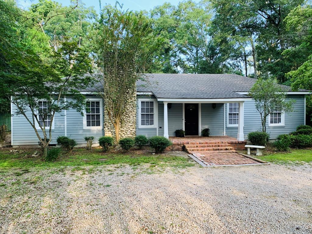 Dont let the charming cabin facade fool you! This 2,770 Sq Ft renovated 1930s charmer host spacious open floorplan with 5 large bedrooms,2 full baths, spacious formal living and dinning room with fireplace, updated kitchen with plenty of counter space, huge laundry and storage room with built in cabinetry. Numerous closets and storage throughout, all with custom built-ins. Large master suite features private sunken sitting room with his and hers walk in closets. 5th bedroom features custom build-ins that would allow the room to be used as office, and is also  perfect for entertaining. Hardwood, tile, and wood laminate flooring throughout. Inviting rocking chair front porch with brick floor and easy access to the  .48 acre lot with privacy fence, storage building, natural landscaping and gravel drive. Well maintained with roof less than 90 days old. Neighborhood just off Dawson Street National Historic Registry District is up and coming!