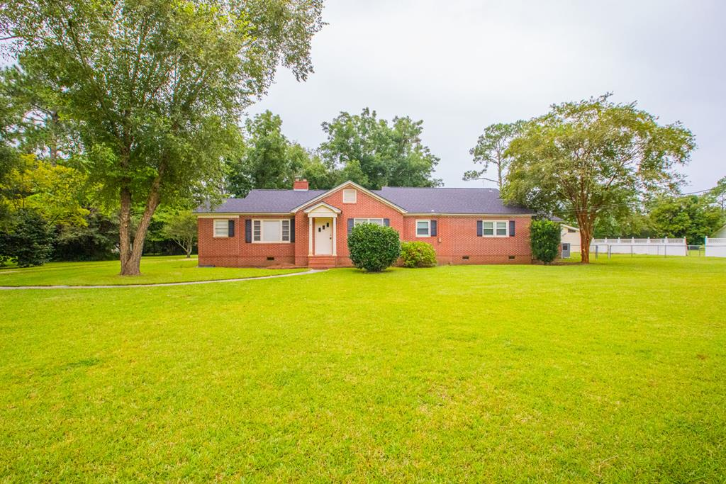 This fabulous brick home boasts 5 bedrooms, 3 full bathrooms, 2 large living rooms, and a dining room. It also has a spacious workshop and almost an acre lot with a few pecan trees. The home has a new roof and new AC unit. This home has so much to offer! There is a side room that could be used as an office with its own entry. Close off one side of the home and use it to run a business. Have a multi-generational family? This home would be great with the separate living rooms and layout. The side yard is also fenced for your furry friends.