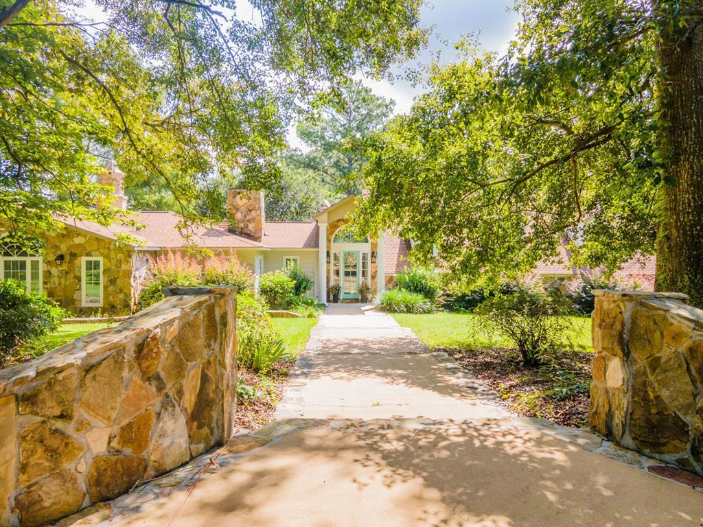 Home at last! Wind down the private road leading to this large but cozy home perched on pretty 19 acres between a pond and a picturesque, income producing pecan orchard. Relax in the downstairs master wing with two fireplaces, huge closet areas, private den, wet bar, an office, and his/her bath with direct access to your patio overlookiing the peaceful pond. Additional perfect entertaining space leads to the chef's kitchen and butler's pantry with high end appliances and a plethora of storage. Two additional bedrooms and bathrooms plus bonus room reside upstairs. This one of a kind, pond views from every room, custom home is close to all things Thomasville but provides the best of primo country living.