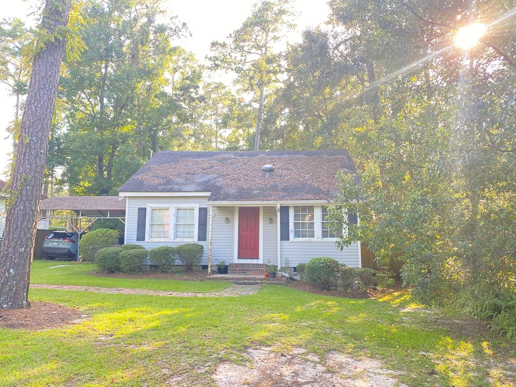 """LOCATION LOCATION LOCATION!!  This charming 3/1 home facing McIntyre Park offers convenience to schools, shops, and downtown eateries. Enjoy your evenings/mornings on the back deck overlooking the private, wooded backyard.  There is a privacy fence, dog kennel, and covered parking for two vehicles.  Upstairs you will find the third bedroom and room to add a second bathroom.  Walk across the street to enjoy the park and the kids can even walk to school!  Priced under market value, there is room to update and make repairs to this """"sold as is"""" home.  See Realtor Remarks for more details."""