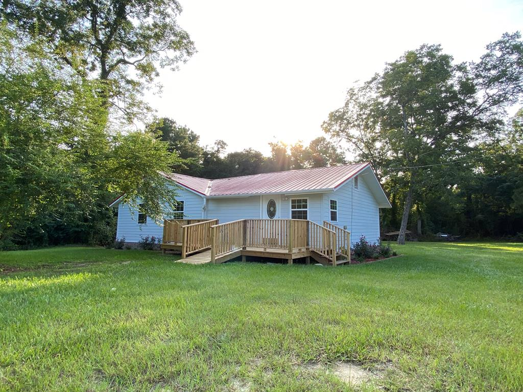 This adorable home sits on 2.5 acres and has been remodeled with new exterior siding and paint, new windows, a tin roof (5 years), new decking, and fresh landscaping around the foundation of the home.  Seller chose very tasteful colors inside beginning with the paint.  New carpet was installed in the bedrooms, and new LVP throughout the common spaces.  There is new tile flooring in the bathroom and a luxury tiled shower.  For the investor, there is even room on the property to build a new home right next door to sell or rent.  See lot layout picture in the listing photos for clarification.  There is ample backyard space and Seller planted several fruit trees.  Owner relocated for work before the HVAC system and kitchen could be installed allowing a fresh palate for the new homeowner to add their own personal touch!