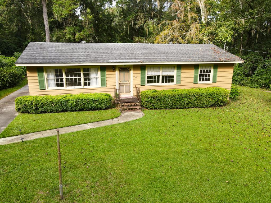 Charming 3 bedroom 1.5 bath cottage located in town and close to downtown Thomasville. Sitting on a 1.84 acre lot, this well equipped home on Partridge Drive is move-in ready!  Perks of this house are a fancy smart fridge that plays music while you cook, large back screened-in porch, grilling gazebo down by the creek, and the large outbuilding with window unit that's perfect for an outdoor recreation space or sleeping loft.  Inside, there's a large living room with built-ins and combined kitchen/dining area; then down the hall are the 3 bedrooms; two of which have it's own toilet and sink with a shared shower/tub combo. The roof is 6 years old; the AC 10 years. The property, but NOT the house, is in a flood zone.  Current owner has flood insurance that can be transferred to the new owner.