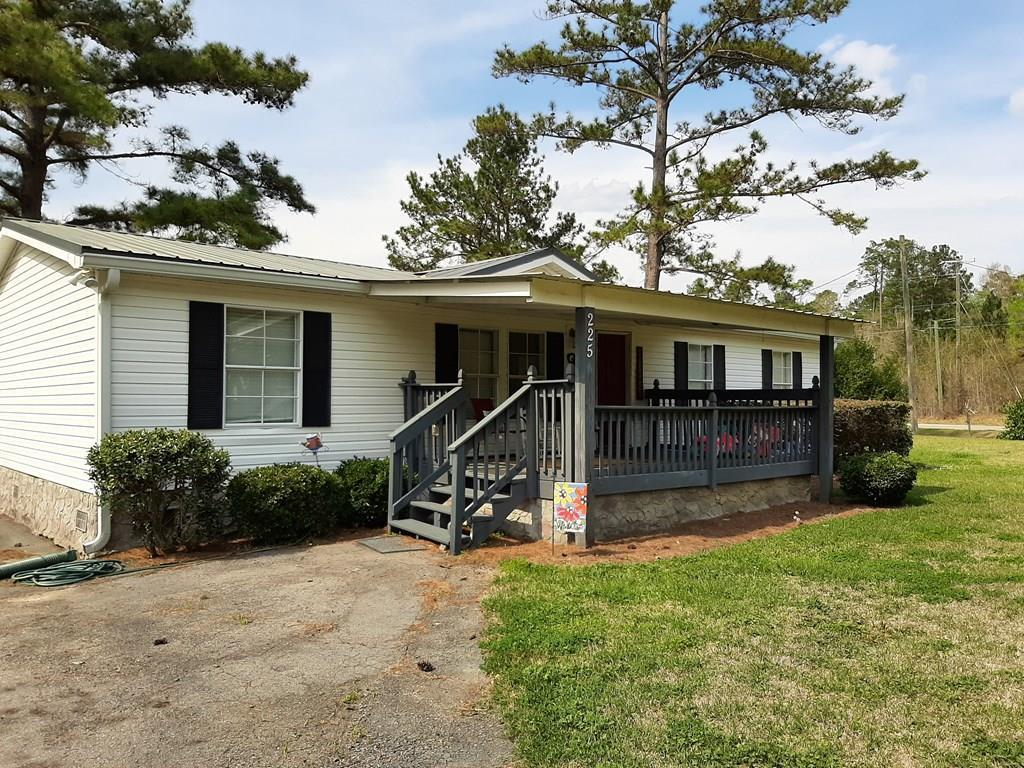 A little bit of country with the convenience of city living.  Split floorplan with 3 bedrooms & 2 baths, dining room, & kitchen with spacious countertops, laundry room along with a front & back porch.  The out buildings are a handiman's dream with ample space for all of the tools & projects. Metal roof on home, shop & carport.  Very private & well maintained. Call for your private tour today!