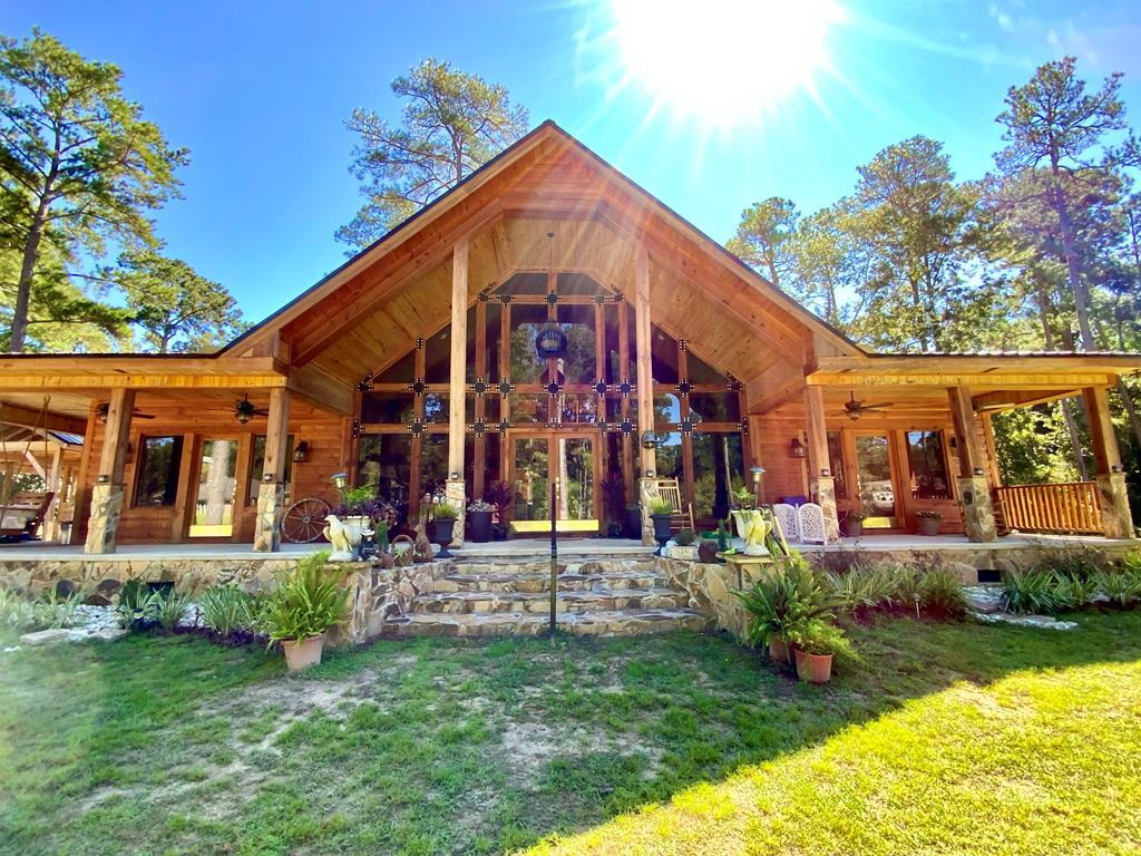 A-Framed custom crafted lodge with open floorplan, soaring ceilings, and plenty of room for the family and entertaining. The chef's kitchen has more than ample space to have everyone stand around the island and enjoy the festivities whether it be a simple family dinner or a holiday party. Custom wood cabinets throughout the home are topped with granite and very unique vessel sinks & fixtures. This is more than just a home! The western red cedar wood frames this log cabin and mountain stone surrounding the wood burning fireplace. Not only is there 2 master suites with exits onto the amazing warp around porch, there is a loft on the second floor that can double for overflow company, office or craft room. The main suite offers a luxury tiled shower, soaking tub, and his and hers vanities. The 3rd room offers an oversized laundry area with mud sink and built in dog washing station. The unique rustic elegance of the oversized Sunroom may very well be your favorite place to begin your days and finish off your evenings. Who could ask for more? This secluded log cabin home is on a private drive of Pebble Creek Pointe and is very secluded and yet has that feel of country with the convenience of being 5 minutes from downtown Thomasville. With almost 1,300 square feet of open porches and deck areas and 1,000 sq.ft. double carport, you will certainly enjoy the peacefulness of rocking and taking in the natural surroundings of this 2 acre parcel.