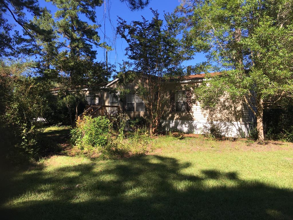 """Here is the perfect opportunity to own  31.58 acres only 1 mile off Hwy 84 and 12 miles from Publix.  The doublewide has 2432 sq ft and has two living areas, 4 bedrooms, 2 baths, a formal dining room and breakfast area in kitchen.  Outside is a pond, shed with a lean to on each side, a greenhouse,  a mancave/party barn with screened porch, and an above ground pool, currently not in use.  There are two sites on property with water and septic tanks currently not being used but great for a """"family"""" community.  A doublewide on back of property is owned by tenant and paying monthly rent for land use.   Make your appointment today."""