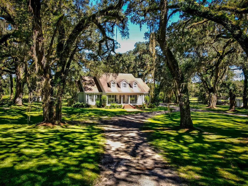 This spacious farm house and guest cottage set on 3.7 acres among mature live oaks draped with spanish moss present the perfect picture of South Georgia living. Constructed in 2001, the primary residence is over 5500 sq. ft. and offers five bedrooms and 4.5 baths along with generous and light-filled living areas. Wood laminate flooring and plantation shutters add to the homes contemporary appeal plus theres crown molding and chair rails for that timeless elegance. The kitchen is a gourmet haven with tons of cabinet space; it includes an island and opens up to the den with fireplace and large breakfast area. The master bedroom with sitting area and built-in cabinets along with 3 additional bedrooms are downstairs and one bedroom upstairs. The long list of gathering spaces includes a formal dining room, sitting room, sunroom, and full office downstairs and upstairs there's a bonus room and game room with wet bar. Other special features include a large laundry room,  surround sound, an alarm system, large back deck, an oversized 3 car garage with storage, and so much more. This house was custom built from the ground up and designed to be energy efficient. New upgraded  AC unit upstairs, new septic system, and a lifetime roof. The 964 sq. ft. one-bed, one-bath guest cottage was built in 2017 and is ready for guests. Inside the cottage is a kitchen, living room, sunroom, pine walls and floors, Jerusalem stone floors plus a screened-in back porch and rocking chair front porch. This property is actually the original settlement of Boston Georgia before it was moved to its current location. If you are looking for a homestead in the country that's close to everything Thomasville offers, this is the perfect place.