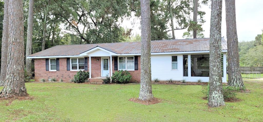 Great property with 2 houses being sold together on 3 lots, less than 5 minutes from Publix!  Main house is a brick 2 BR/1BA with 1,566 sq feet with brand new HVAC system,  a metal roof that is about 17 years old,  and a great job of updating by the current owners. It has a large open kitchen with plenty of cabinets and a gas fireplace off of the dining room in the family  room that can heat the house on cold days.   It also has a huge shop with water and power and a concrete floor.  The 2nd home is a 1999 Grand Manor mobile home with 3 BR/2BA.  It has tile in the dining room and kitchen, newer laminate flooring, and the HVAC is 5 years old.  It really has a lot of space.  Both properties are in excellent condition and are being offered together.  You can buy these and rent one out and live in the other!  If you are looking for a turnkey rental investment, this is a good option with everything ready to go!  Come see this one before it is gone.