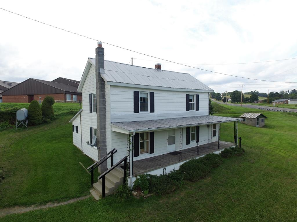 Farmhouse and .711 acre next to new school in Grayson County. Close to school (walking distance)  Near Mt Rogers State Park and horse trails.  Great starter home with low maintenance vinyl siding and metal roof.  Nice laying yard with garden area and small stream in front.  With a little love and some remodel this home could be your home for years to come.