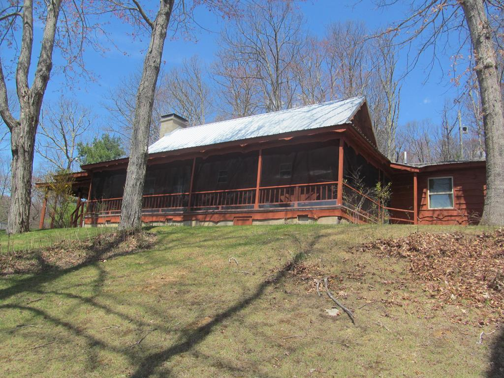 Rustic cabin with 11.875 private acres nestled in the majestic Blue Ridge Mountains of Grayson County, VA. This property is the perfect place to get away from it all; relax, play, or just sit on the front screened porch enjoying all the sights and sounds that Mother Nature has to offer!  Warm and inviting cabin boasts 1,575 square feet with open kitchen, living room, dining area, large laundry/mudroom, 3 bedrooms and 2.5 baths.  Home features beautiful cherry shiplap interior walls , exposed wood beams, masonry fireplace with wood stove insert for those chilly mountain nights.  Acreage is mostly wooded with mature trees, rock outcroppings and springs.  Barn and shed with electricity for extra storage, workshop, etc.  Elevation is approximately 3,700 feet.  Located close to New River, National Forest, horseback/hiking trails, stocked trout streams and Mt. Rogers/Creeper Trail, and Blue Grass Festivals.  Don't miss out on this opportunity to own a piece of the Blue Ridge Mountains!