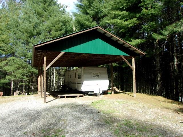 34 wooded acres with privacy & seclusion.  27 ft. Trail Harbor Camper with slide out.  Electric & septic.  The camper sits on a concrete patio with a canopy.  Land is all wooded with white pines and hardwoods.  Small stream.