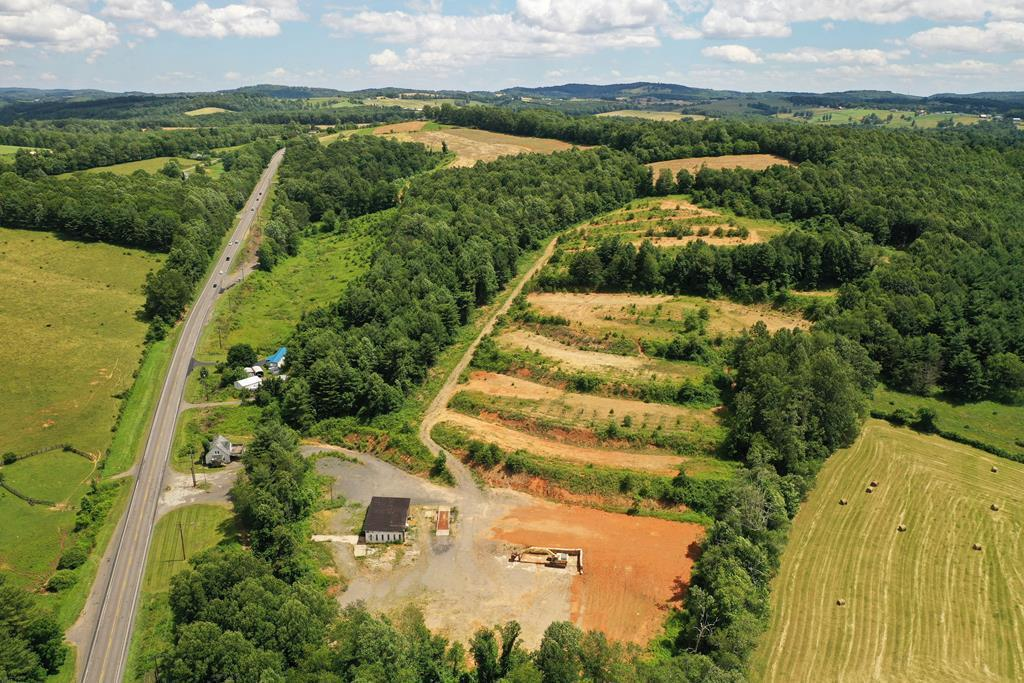 This beautiful hillside property is located just outside of the town of Hillsville. It boasts 465 ft of road frtg. on busy Hwy 52. A portion of this property is occupied by a 2448 ft. garage, complete with hydraulic lift, and drive over cargo scales, office area & retail space. On another acre sits a 1642 ft. Cape Cod style home that was previously used for storage and office space. The balance of the 24.3 acres could be subdivided, giving endless possibilities to facilitate most any business plan. This property would be a great location for a medical facility, motel, or mountainside resort cabins,  campground, micro-brewery, legal practice, accounting firm, retail outlets, church, automotive center, or educational facility. This property is close to the Blue Ridge Parkway, I 77, at 81, Highway 58, the New River, and New River trails, medical offices, schools, and shops,