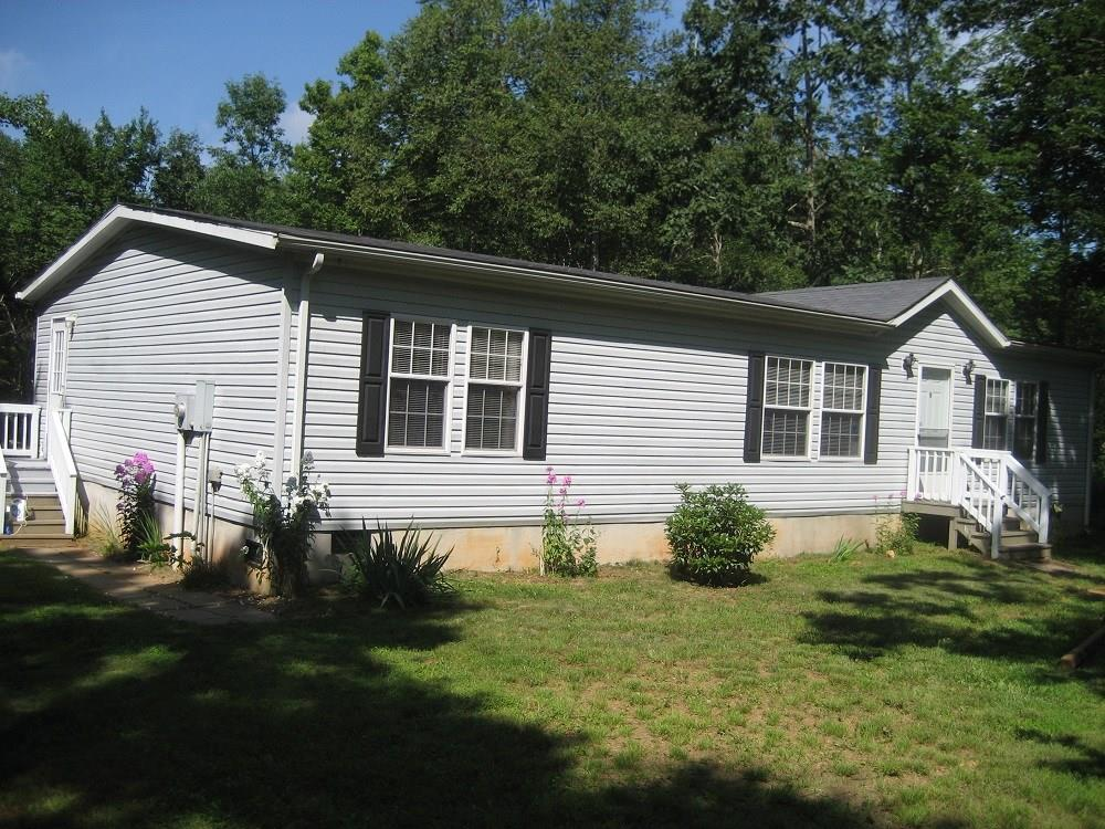 Built in 2010, this beautifully spacious Double Wide on permanent foundation is in a beautiful serene setting close to downtown Meadows of Dan. The 4.84 acres is mostly wooded with lots of road frontage to possibly subdivide into 2-2.5 acre lots. The home is extremely well kept with large spacious rooms and an open floor plan for kitchen, dining and great room. The kitchen has an oversized island with counter and cabinets for lots of workspace and storage. The mudroom has W/D hookup. The Master Bath is furnished with a large garden tub. The grounds include a 1 car detached garage and additional garden shed. Internet to be verified by Buyer.