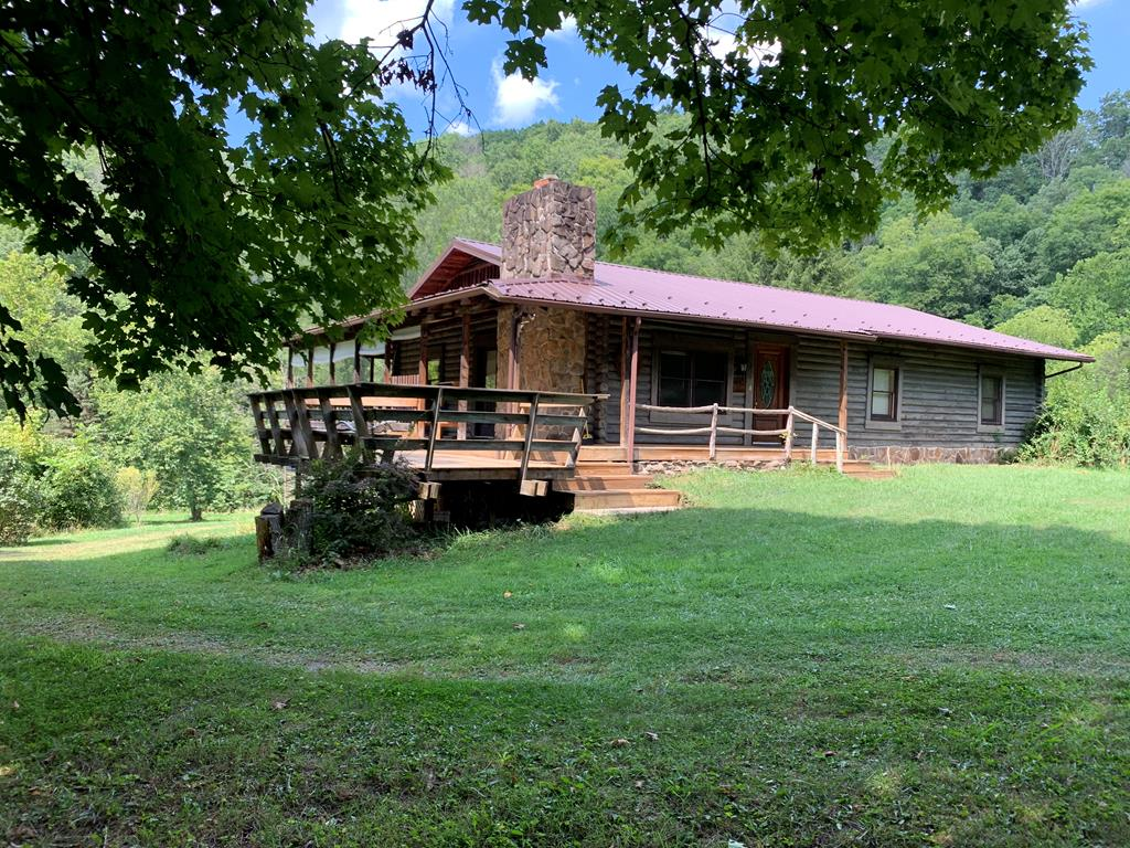 Rarely does a property of this caliber hit the market!  Custom-built log cabin with real rock. The outer interior walls being pine logs and the interior being drywall.  Situated on 5.07 acre site surrounded on three sides of the Clinch River. Lay lays almost level with awesome views and access. You can drive the entire property.   Relax on the wrap-around porch and enjoy pure solitude.  Lots of wildlife. Custom woodwork throughout offering oak hardwood flooring, Wormy Chestnut cabinetry, pine ceilings.   Basement offers so much potential for additional living space.  Spacious 1 car attached garage. Detached garage/workshop. Dairy. Must see to appreciate the uniqueness of the home and site.