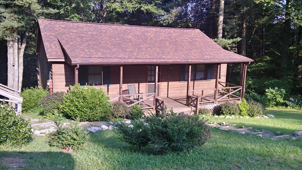 A mountain cabin in a well established community just off the Blue Ridge Parkway. A very neat 2 bedroom, 1 bath cabin with a view of a small spring fed creek from the 36 foot rear covered deck.Neat and clean with newer roof, appliances and flooring.Unique work shop/storage area below rear deck.Lots of privacy  as the adjacent two lots are to be conveyed with this cabin. Prior owners live herd year round. Enjoy the clubhouse, community pool or tennis courts. Also, shuffleboard, horseshoes and fishing ponds are also available. Join us for community event at the gazebo. It's a great place to call home.Many residents live here all year long. Community provides trash site and snow removal when necessary.  Buyer responsible to check for internet service.