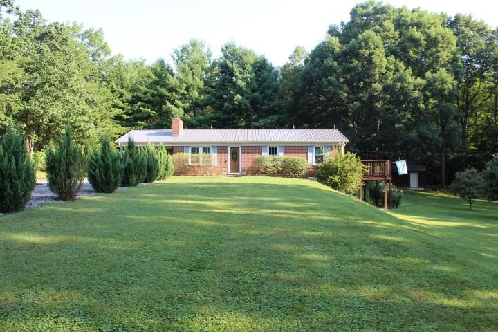 "Ranch Style Home  (25' x 43') in excellent condition with unfinished basement located in Patrick County, VA (2341 Doe Run Road, Ararat, VA 24053,  Main level: Kitchen (10'6"" x 9'10""). Laminated hardwood which is water proof and scratch proof.  Dining Area  (8' x 10'6"") Table and chairs will convey. Living room  (12'3"" x 16'6"") with wood burning fireplace and hardwood floor. Bedroom (8' 10"" x 9'6"") hardwood floor. Full Bath (5' x 7'8"")  Tile Floor. Bedroom (12' x 9'10""). Master Bedroom (10'6"" x 12') Hardwood Floor. Master Bath ( 8' x 5') Tile Floor. Double Pane Double Hung windows.  Energy Efficient lights. Each Room has individual electric heat units mounted on wall. Each Bedroom has a ceiling fan. Unfinished basement with walkout. Stackable Washer and Dryer, Dehumifer, Freezer and Table with 6 chairs will convey. New insulation on ceiling. New water heater.  From basement - walkout to Patio (18' x 12').  Security System.  Deck (34' x 12')  Carport  (13'5"" x 25') attached to house."