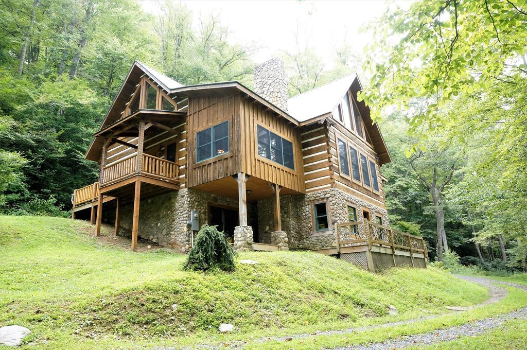 Beautiful Hand Hewn Log Home on 7.8 acres over looks 400 ft Bold Creek frontage on Little Reed Island Creek. Walls are a 12inch solid Log, Chinked inside and out, with Dove tail corners. This custom built cabin has over 2400 sq ft and offers two master suites and large loft that is open to below, enormous glass front Living room with a stone, wood-burning fireplace. The large open  kitchen is well equipped with a  Jenn-Air Range, trash compactor, built in Ice maker and large walk in pantry and separate dining room overlooking the creek.  Cathedral and vaulted ceilings with hand hewn beams in every room. Pine hardwood flooring in main living areas, tile in bathrooms and carpet in the bedrooms. Full walk out basement is ready to finish and has a flu and wood burning stove in place. Creek Views from almost every room! The craftmanship here is a must see.