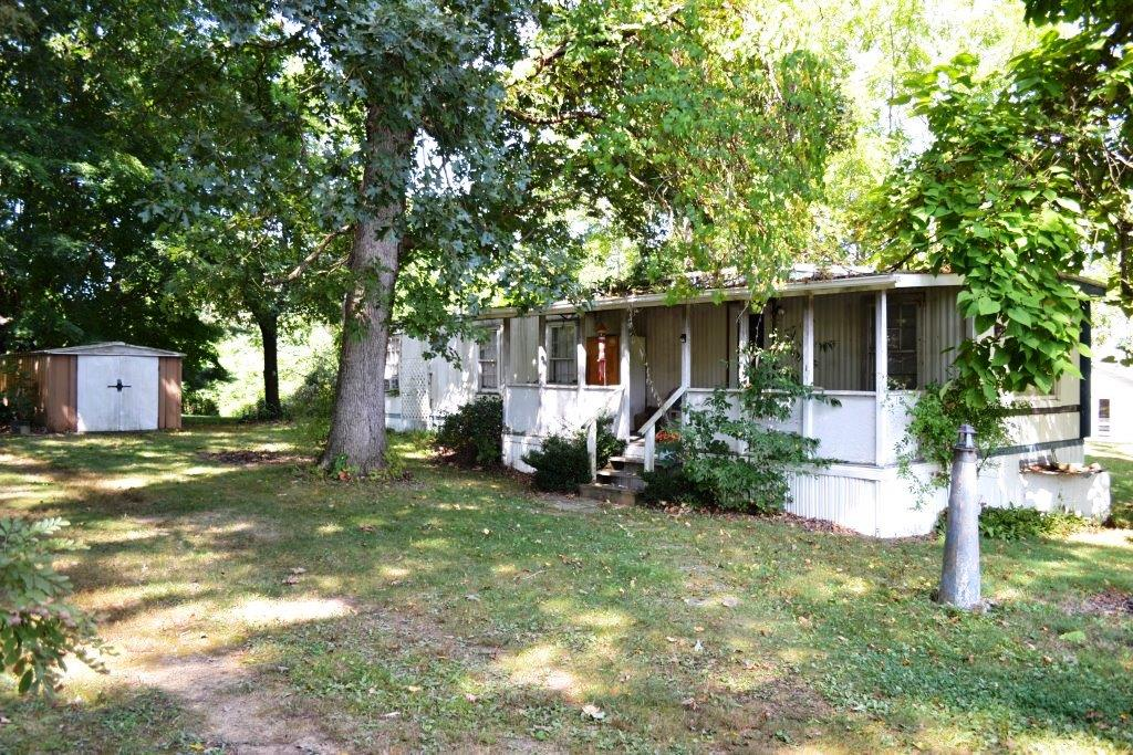 Singlewide home on 1 acre wooded lot with lots of perks. Although dated, this comfortable home with gas heat has large gathering space and addition opportunities . The remainder of the property has one partially finished shop building with loft and another storage building framed-in, a chicken coop with attached pen, as well as a metal building for all the toys. This lot is ready for a bigger home as there's a well and 2 bedroom septic with another 3 bedroom septic already in place near the rear of the property. The lot is level and full of beautiful walnut trees and with the infrastructure already in place, this property could become your new home site with space for others in the buildings when completed. There's room for a few animals and is close to New River and New River Trail for those just seeking the perfect getaway spot.