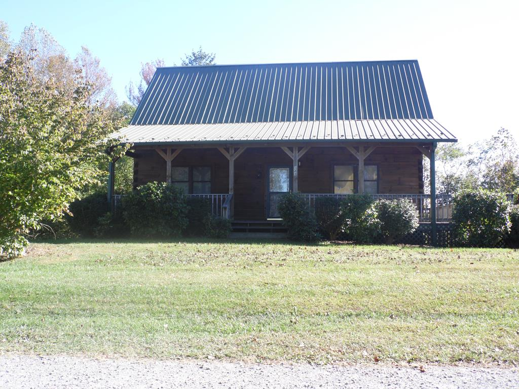 Have you been looking for an affordable log cabin?  Well here it is.  1512 square feet, 3 bedroom, 2 bath situated on 1.75 +/- acres, built in 2003,  full unfinished basement with a drive under 1 car garage.  This charming log cabin is located on one of the highest elevated county roads in Carroll County.  When you walk through the front door you will find an open concept living room and kitchen with hardwood floors, exposed ceiling beams, and a bright and welcoming feel.  The bedrooms are spacious, and the loft area is the perfect place to get away.  Outside you will enjoy the wrap around deck, which is just calling for some rocking chairs, so that you can relax and take in the views.  With some tree removal in the back yard you could potentially open up additional views.  This home is perfect for a primary residence or second home, with it's convenient location to I77, you are just minutes from Galax, Hillsville and Mt. Airy.  The cabin is in need of some exterior maintenance,