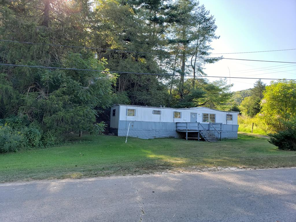 """This property has endless opportunities! Offering 12 acres of mostly wooded land with a 1973 singlewide serviced by private septic and county water.  The land would be perfect for hunting or could be cleared and used for agricultural purposes.  The home will be sold """"as-is"""" but could be repaired, replaced, or you may choose to build a new home on the top of the hill.  The sky's the limit!  Priced below tax assessed value!"""